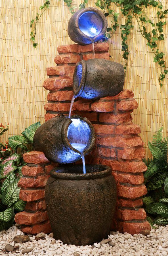 Fuente c ntaros de agua sobre pared de ladrillo luces - Fuentes de jardin de pared ...